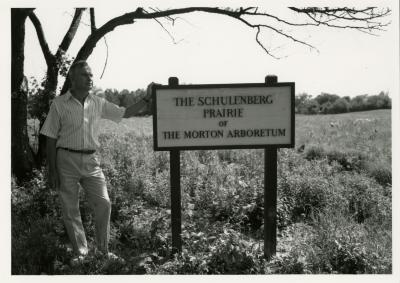 Ray Schulenberg with prairie sign in the Schulenberg Prairie