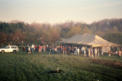 Crowd gathered near yellow stripe tent for Earth Day celebration and berm planting