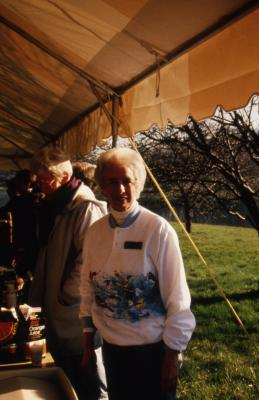 Helen Langrill next to refreshment table in tent during Earth Day celebration and berm planting