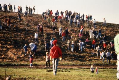 Boy in red coat looking at crowd on berm during Earth Day celebration and berm planting