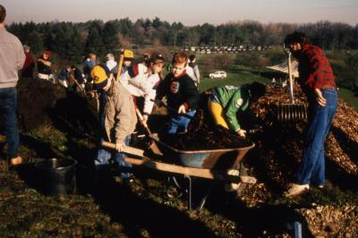 Children loading wheelbarrow with mulch during Earth Day celebration and berm planting