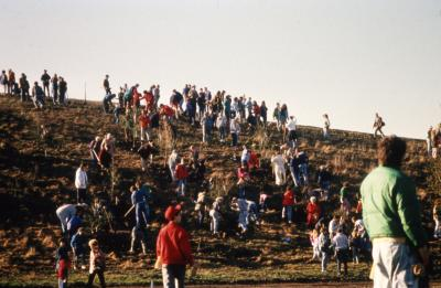 Crowd ascending berm for Earth Day celebration and berm planting