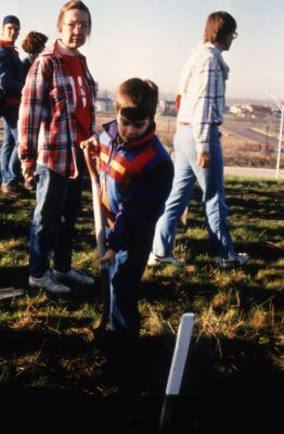 Woman supervising young boy with shovel during Earth Day celebration and berm planting