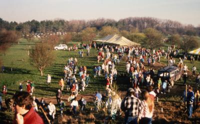 View from top of berm of crowd and yellow stripe tent during Earth Day celebration and berm planting