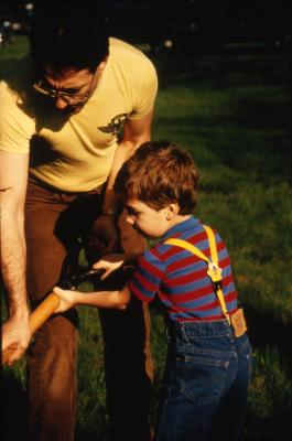 Man holding shovel with young boy during Earth Day celebration and berm planting