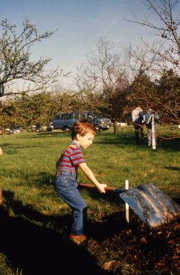Small boy with big shovel turning over soil during Earth Day celebration and berm planting