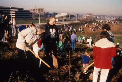 Bill Hess and others planting tree on top of berm during Earth Day celebration and berm planting