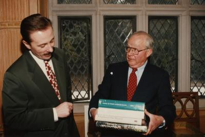 George Ware Retirement Party in Founders Room - George Ware holding stack of books with Gerry Donnelly