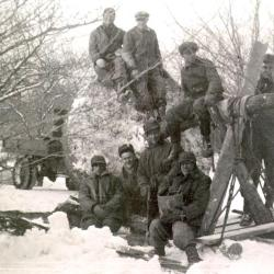 Eight men (Roy Burnside at bottom left seated) seated on and around root balled tree on sled in winter snow