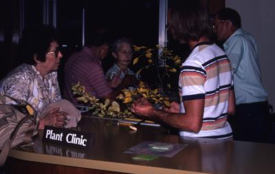 Chad Avery reviewing plant specimen at Plant Clinic desk with visitor