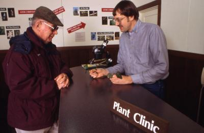 Bill Dreyer helping visitor in Plant Clinic