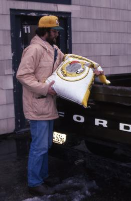 Duane Henry loading bag of bird seed into truck