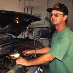 Mike Abel working in garage with truck hood open