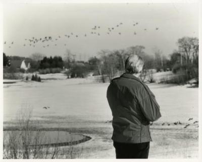 Alfred Etter observing ducks & geese in flight over Arbor Lake in winter