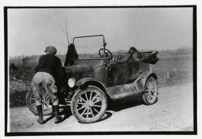 Clarence E. Godshalk with Model T car and dog Punch