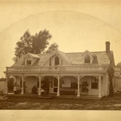 Carl Morton sitting on porch in front of Arbor Lodge house
