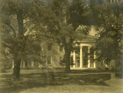 Arbor Lodge, partially obstructed view of side rotunda portico through trees from lawn