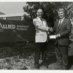 Dr. Marion Hall receiving check and shaking hands with man in front of Allied Amphenol Products