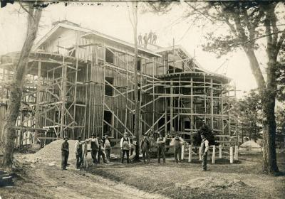 Arbor Lodge remodeling construction, house with rotundas framing erected, workmen in front