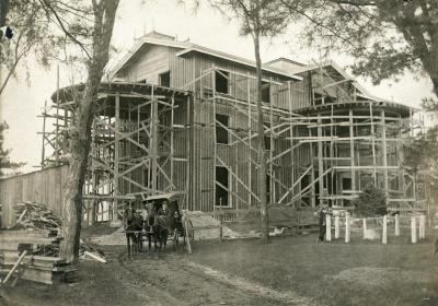 Arbor Lodge remodeling construction, house with rotundas framing erected, carriage and two men in front