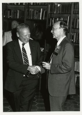 Dr. Marion Hall and Charles Haffner III shaking hands at party in Library