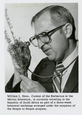 Dr. William Hess using a lens to examine a plant