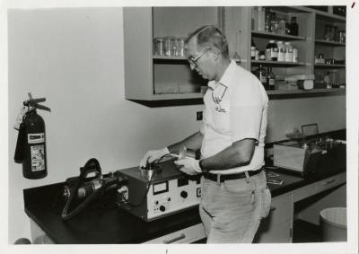 Dr. William Hess placing disc flower (on stage) into the sputter coater