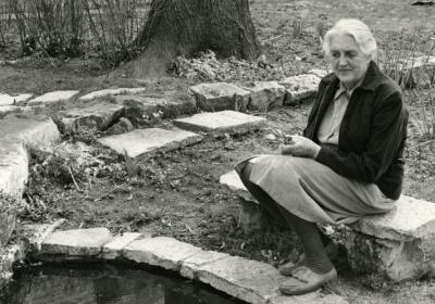 May Theilgaard Watts, seated on bench at a pond in her garden at home in Naperville
