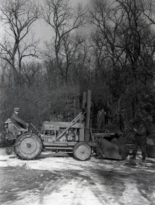 Clarence Godshalk driving Arboretum's first international tractor with front end loader carrying tree