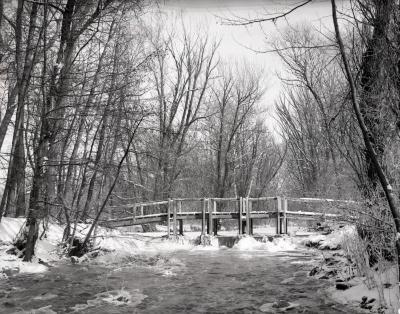 Wooden bridge across DuPage River dam in winter