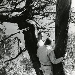 Dr. Marion T. Hall with Dick Young leaning against 850 year old juniper along bluffs of the Fox River