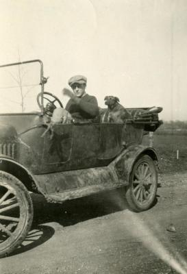 Clarence E. Godshalk and his dog, Punch, inside Joy Morton's castoff Model T car