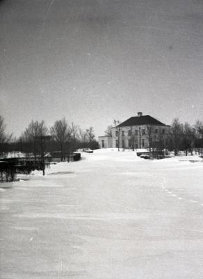 Distant view of Arboretum Center from snow covered Hedge Garden