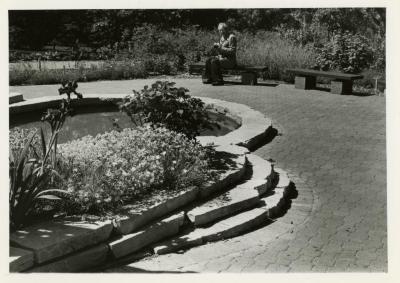 John Kohout seated on bench in Fragrance Garden