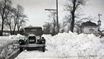 Clarence Godshalk's Model A Ford Roadster on snow covered road, South Farm in background