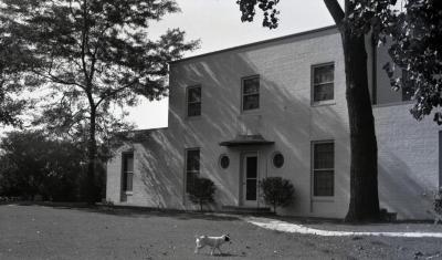 Clarence Godshalk's second Arboretum house, exterior front view from side, dog in lawn