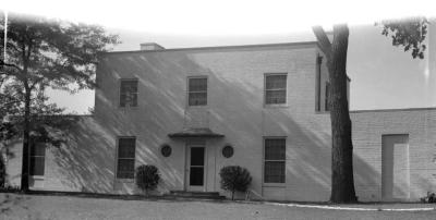 Clarence Godshalk's second Arboretum house, front view, dog near shrub next to stairs