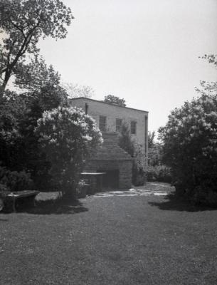 Clarence Godshalk's second Arboretum house, view of backyard with stone fireplace