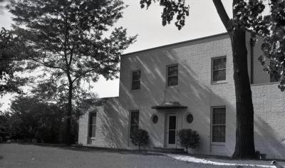 Clarence Godshalk's second Arboretum house, exterior front view from side, dog sitting in lawn