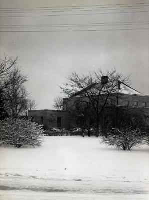 Administration Building, side view in winter partially obstructed by bare trees