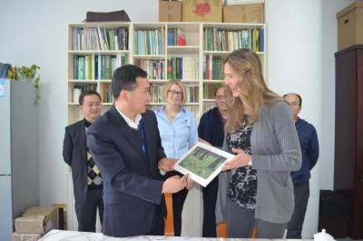 Nicole Cavender and Murphy Westwood presenting a photograph to colleagues at the Chenshan Shanghai Botanical Garden in China
