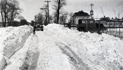 Clarence Godshalk's Model A Ford Roadster in distance on snow covered road, South Farm in background