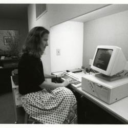 Sterling Morton Library staff, Rita Hassert seated at computer near circulation desk