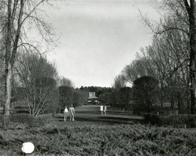 Visitors strolling through Hedge Garden with Four Columns in distance