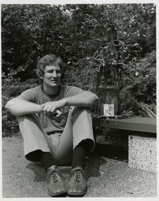 John Slavic seated on ground with oak puppet
