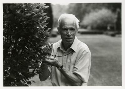 Floyd Swink ouside standing next to plant
