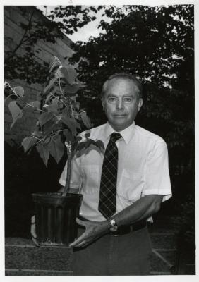 George Ware outdoors holding plant