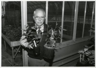 George Ware holding potted greenhouse seedlings from China Collection