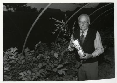 George Ware holding plant in quonset hut