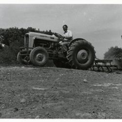 Tony Tyznik driving tractor over landscape